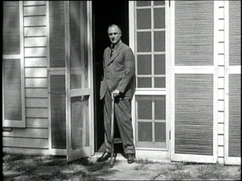 new york governor franklin d roosevelt stands with a cane in a doorway in 1930 - 1930 stock-videos und b-roll-filmmaterial