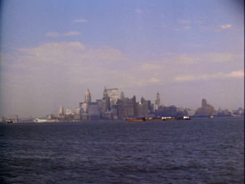 stockvideo's en b-roll-footage met new york harbor, statue of liberty, ellis island / statue of liberty / skyline of lower manhattan from across harbor / freighter barge sailing in... - 1965