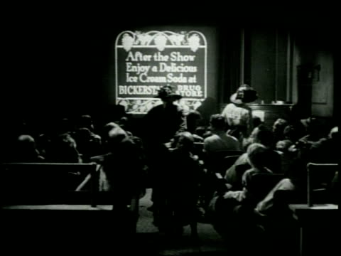 new york in 1900 / new inventions to communicate the american idea / movie theater / a film is hand cranked / people enter and leave the seating area... - nickelodeon bildbanksvideor och videomaterial från bakom kulisserna