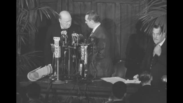 new york mayor william o'dwyer presents former british prime minister winston churchill with a document and they quietly converse behind bank of... - frond stock videos & royalty-free footage