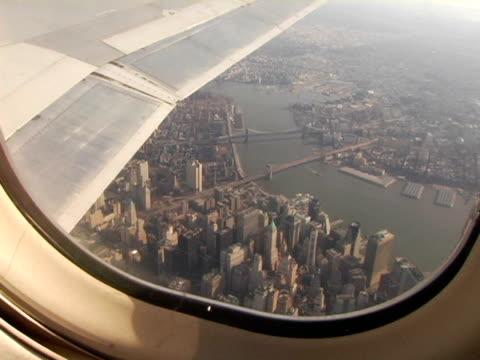 ws, usa, new york, new york city, lower manhattan seen through airplane window - fensterfront stock-videos und b-roll-filmmaterial