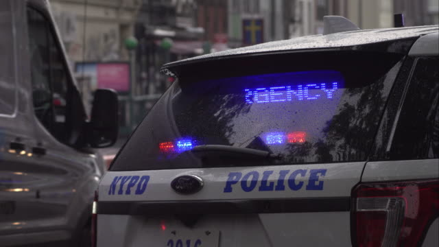 New York Police Department vehicle with scrolling emergency text in back window parked on busy New York street.