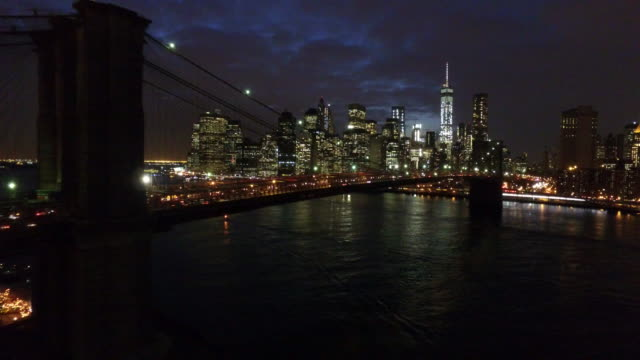 AERIAL: New York skyline, Brooklyn Bridge by night