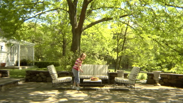 ws, usa, new york state, bedford hills, girl (6-7 years) running up and seating at outdoor seating area in back garden - 6 7 years stock videos & royalty-free footage