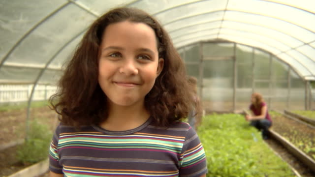 cu, usa, new york state, bedford hills, girl (8-9 years) standing in greenhouse vegetable garden, portrait - 8 9 years stock videos & royalty-free footage