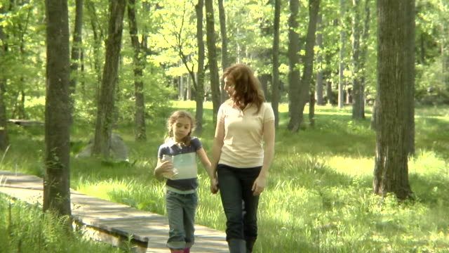 ws, usa, new york state, bedford hills, mother and daughter(6-7 years), walking on boardwalk in forest then looking at jar with water sample - 6 7 years stock videos & royalty-free footage