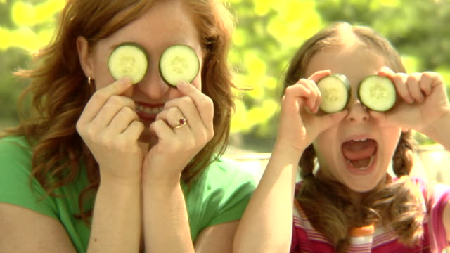 cu, usa, new york state, bedford hills, mother with daughter (6-7 years) holding cucumber slices against eyes, portrait - 6 7 years stock videos & royalty-free footage