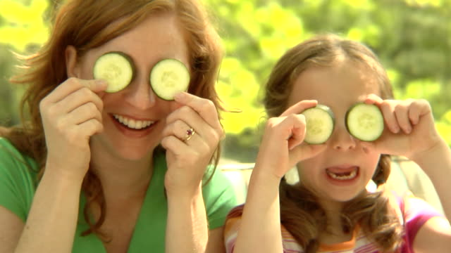 cu, usa, new york state, bedford hills, mother with daughter (6-7 years) holding cucumber slices against eyes - 6 7 years stock videos & royalty-free footage