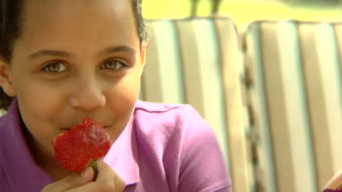 cu, usa, new york state, bedford hills, two girls (6-9 years) eating strawberries, sitting outdoors - 6 7 years stock videos & royalty-free footage