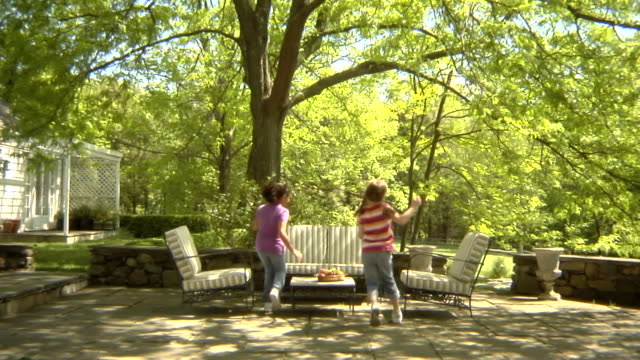 stockvideo's en b-roll-footage met ws, usa, new york state, bedford hills, two girls (6-9 years) running up and seating at outdoor seating area in back garden - 6 7 years