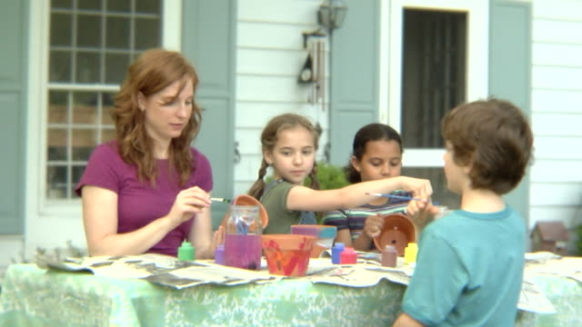 stockvideo's en b-roll-footage met ms, usa, new york state, bedford hills, woman with children (6-9 years) painting pots at front of house - 6 7 years