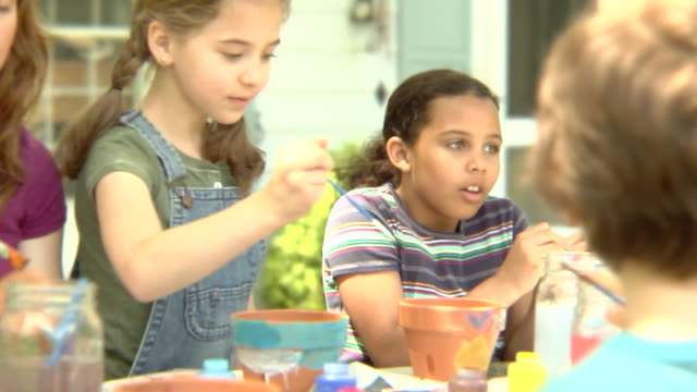 stockvideo's en b-roll-footage met cu, pan, usa, new york state, bedford hills, woman with children (6-9 years) painting pots outdoors - 6 7 years