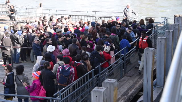 New York, United States: Line up of tourists to get the nautical cruise in the East River toward the Statue of Liberty