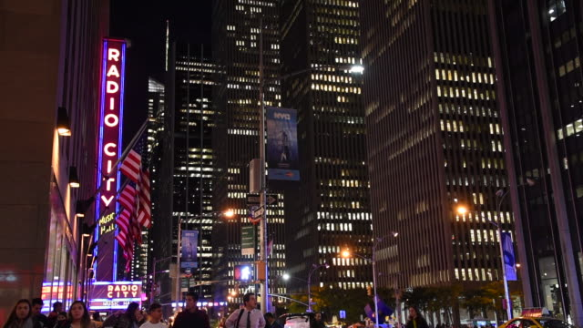 new york, united states: radio city sign and city lights at night in the downtown district - radio city music hall stock videos & royalty-free footage