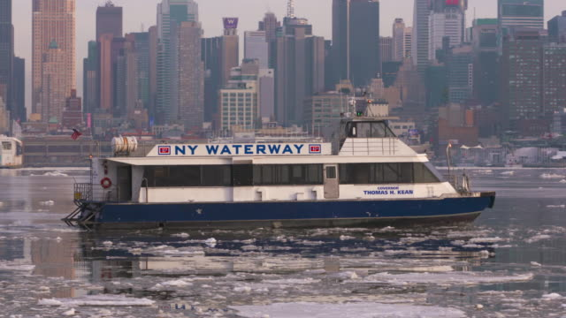 new york water taxi navigates its way through the icy hudson river waters toward the manhattan skyline. - water taxi stock videos & royalty-free footage