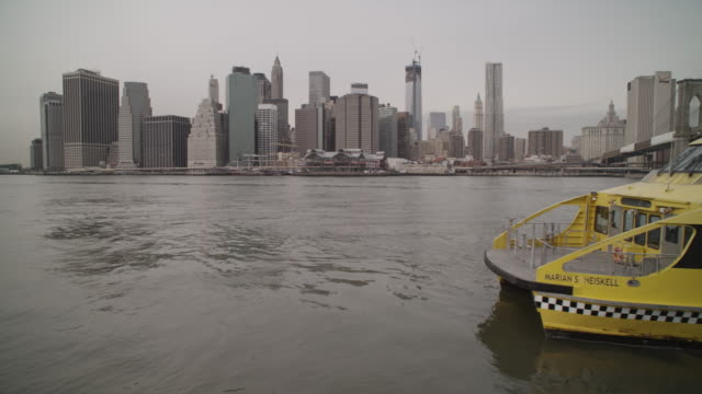 new york water taxi passes along east river in front of manhattan - 水上タクシー点の映像素材/bロール