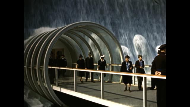 stockvideo's en b-roll-footage met new york world's fair electrical utilities pavilion people walking through glass tube bridge underneath waterfall 1939 world's fair electrical... - 1939