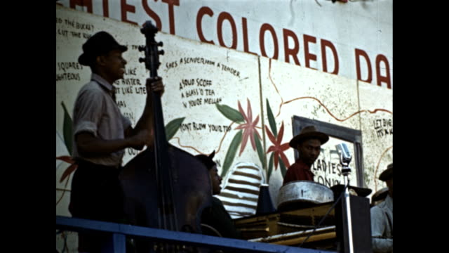 new york world's fair - savoy dance club pavilion, crowd walking by / african american jazz musicians on stage -bassist, drummer, guitarist and... - jazz stock videos & royalty-free footage