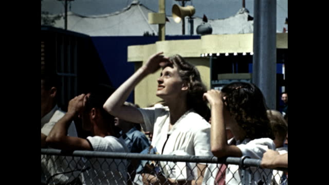 new york world's fair title 'rubber necks on parade' / people watching looking up / children on bench looking pointing men women teenagers looking up... - shielding stock videos & royalty-free footage