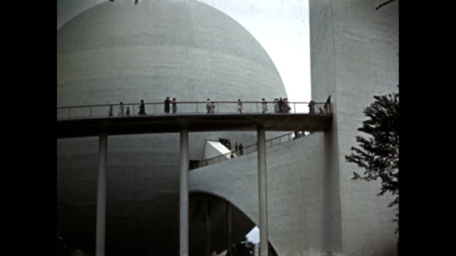 new york world's fair trylon and perisphere montage of people moving across elevated walkway between the two people walking through atrium of trylon... - flushing meadows corona park stock videos and b-roll footage