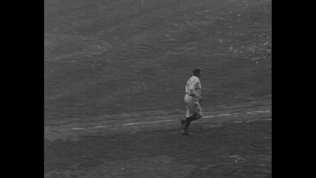 new york yankees player babe ruth hits home run, gingerly rounds bases / view of yankee stadium with stands decorated with bunting / ruth trots from... - ニューヨーク・ヤンキース点の映像素材/bロール