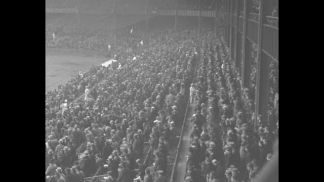 New York Yankees player Lou Gehrig hits and runs to first base / LS Yankee Stadium crowd in stands on their feet and then sitting down / Gehrig hits...