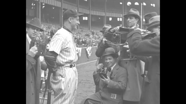 MS New York Yankees player Lou Gehrig in uniform stands surrounded by photographers / CU Gehrig / section of Yankee Stadium stands filled with...