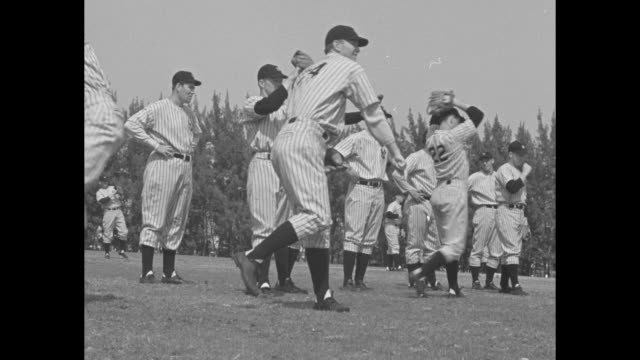 new york yankees players pose for team photo, taking caps on and off, during spring training in florida / manager joe mccarthy stands with coaches,... - チーム写真点の映像素材/bロール