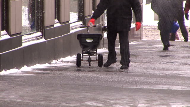 new yorker spreads salt on slippery sidewalk - salt mineral stock videos & royalty-free footage