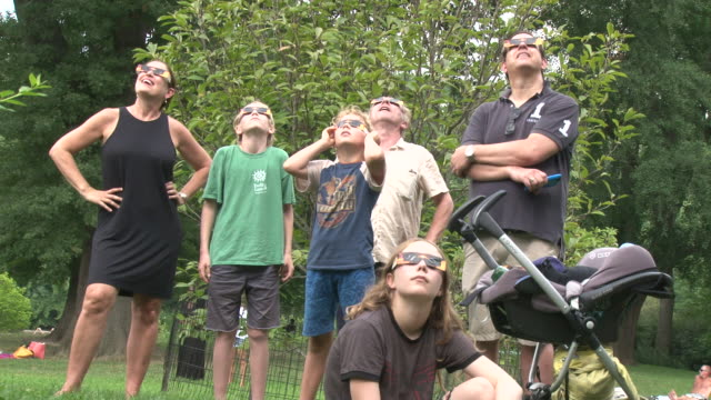 new yorkers take to central park to view the solar eclipse / views from various lawn areas around the park / sequence includes people looking through... - solar eclipse glasses stock videos and b-roll footage