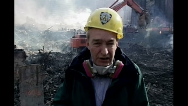 new york's toxic dust threat from 9/11 attacks tx channel 4 news presenter jon snow reporting from scene with respirator round neck snow talking with... - september 11 2001 attacks stock videos & royalty-free footage
