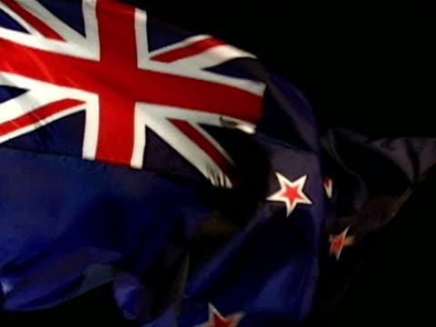 New Zealand country flag flying against black BG Blue w/ flag of UK in upper hoist corner red stars outlined in white represent the Southern Cross...