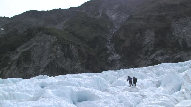 stockvideo's en b-roll-footage met new zealand, franz josef glacier. two men hiking. editorial use only. - men