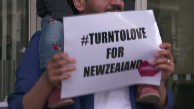 49 dead in mass shootings at two mosques in Christchurch ENGLAND London EXT Man with child on his shoudlers holding '#TurnToLove for New Zealand'...