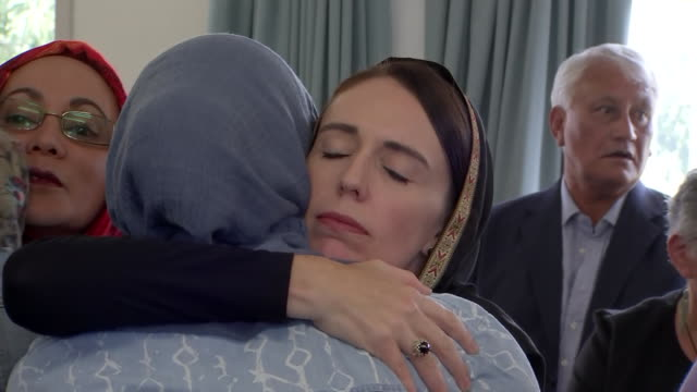vídeos de stock, filmes e b-roll de new zealand prime minister jacinda ardern wearing hijab embracing women at meeting following christchurch terrorist attacks - primeiro ministro