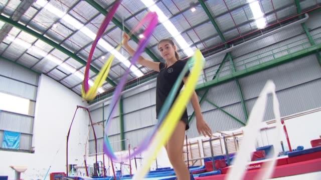 New Zealand Rhythmic Gymnast Stella Ebert twirling rhythmic gymnastics ribbon