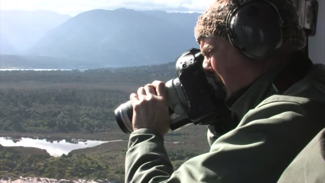 vidéos et rushes de new zealand, south island. photographer taking photos from a helicopter. editorial use only. - photographe