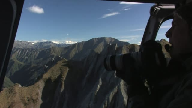 new zealand, south island. photographer taking photos from a helicopter. editorial use only. - only mature men stock videos & royalty-free footage