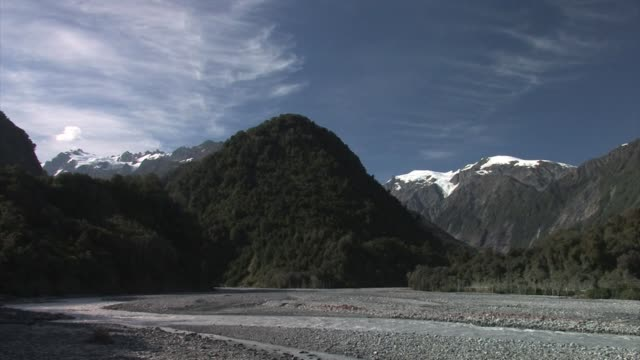 New Zealand, South Island, West Coast Region. Waiho River with mountains in background.
