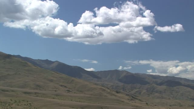 new zealand. south island. white clouds and blue sky over brown and green hills. - new zealand stock-videos und b-roll-filmmaterial