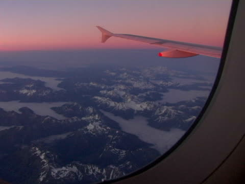 stockvideo's en b-roll-footage met ws, new zealand, southern alps seen through airplane window at dawn - aircraft point of view