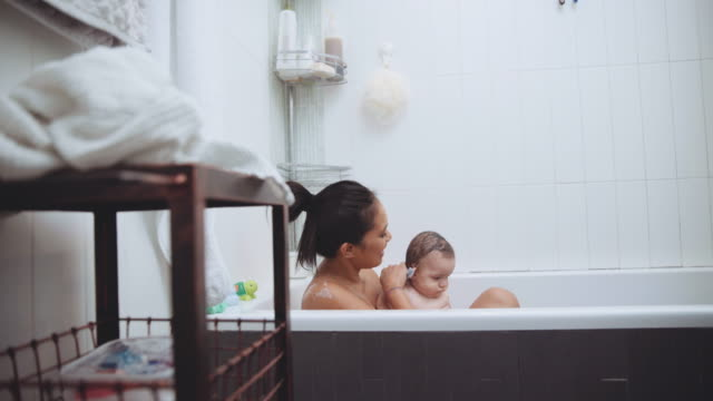 newborn baby and his mother bathing