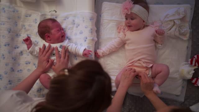 vídeos y material grabado en eventos de stock de bebé recién nacido llorando debido a calambres mientras su hermana lo mira mientras la madre se cambia de ropa - cambiar pañal