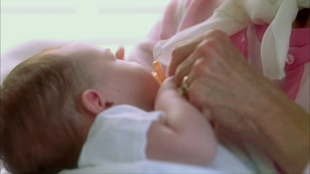 vídeos y material grabado en eventos de stock de cu pan newborn baby girl (0-1 months) in arms of proud grandmother and new mom / tampa, florida, usa - bebés 0 1