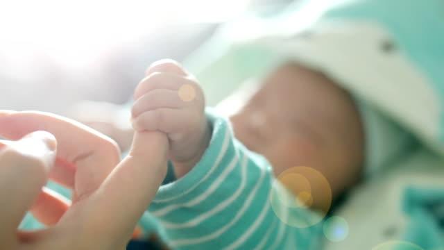 vidéos et rushes de bébé nouveau-né tenant la main mère - famille d'accueil