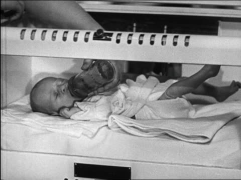 b/w 1948 newborn baby in incubator in hospital being fed with bottle / michigan / medical industrial - 1948 stock-videos und b-roll-filmmaterial