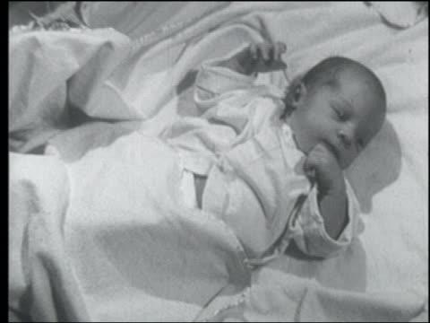 B/W 1955 newborn baby lying in crib