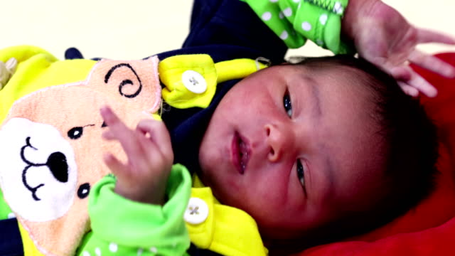 newborn baby playing alone on bed - video portrait stock videos & royalty-free footage