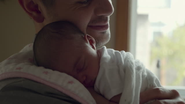 newborn baby smiles as his father holds him - stringere tenere video stock e b–roll