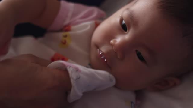 両親の指を持つ新生児 - 見つめる点の映像素材/bロール